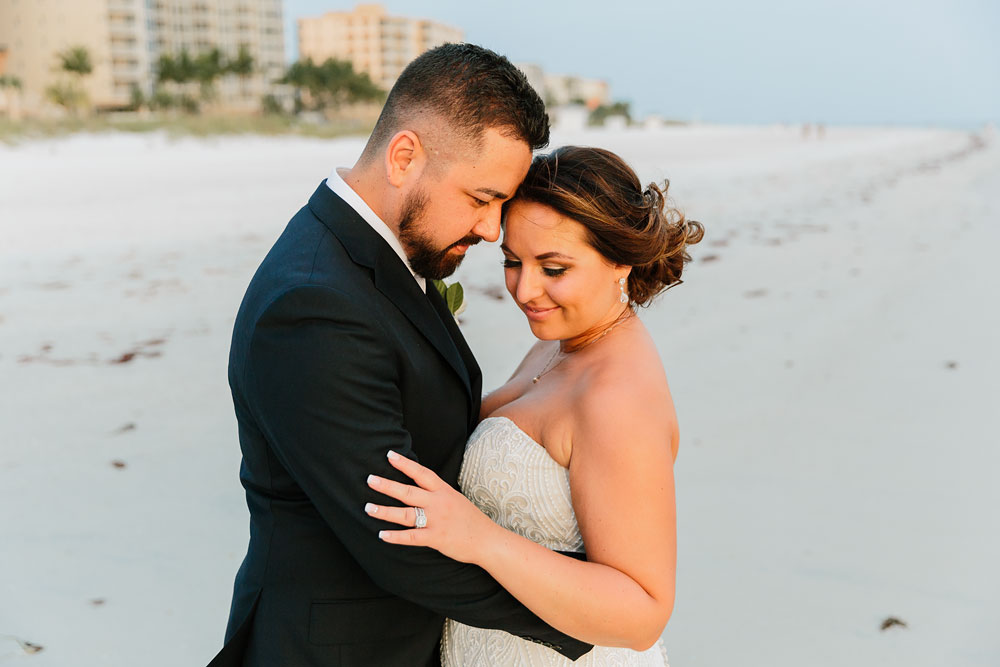 bride and groom hugging on beach at destination wedding  at Pink Shell Resort in Fort Myers Beach, FL