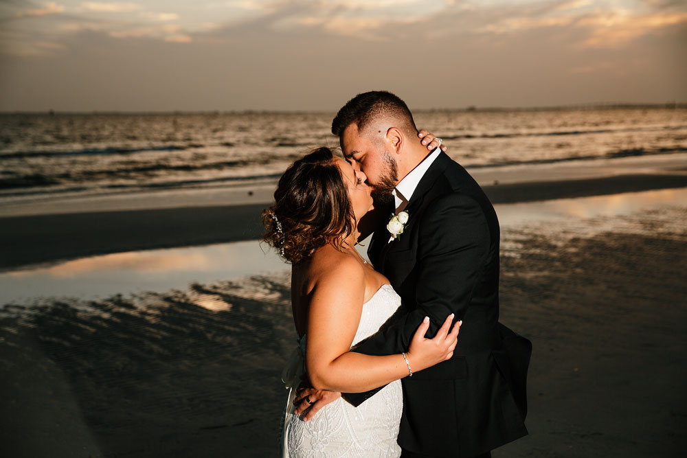 bride and groom kissing on beach in front of ocean during sunset