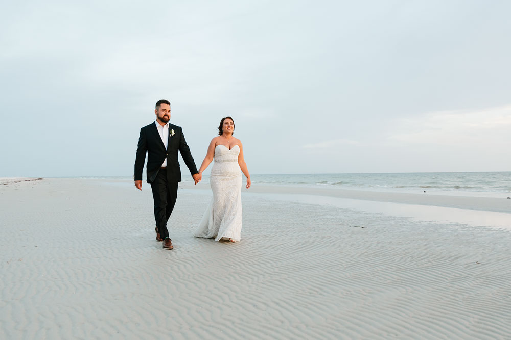 bride and groom walking along beach holding hands