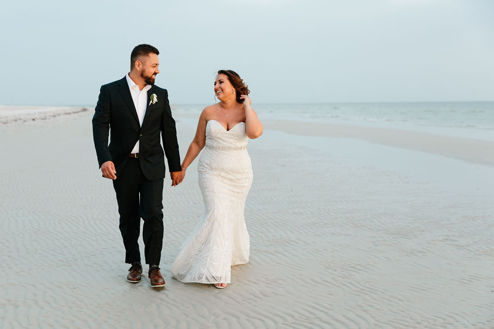 bride and groom walking along beach holding hands and smiling at each other