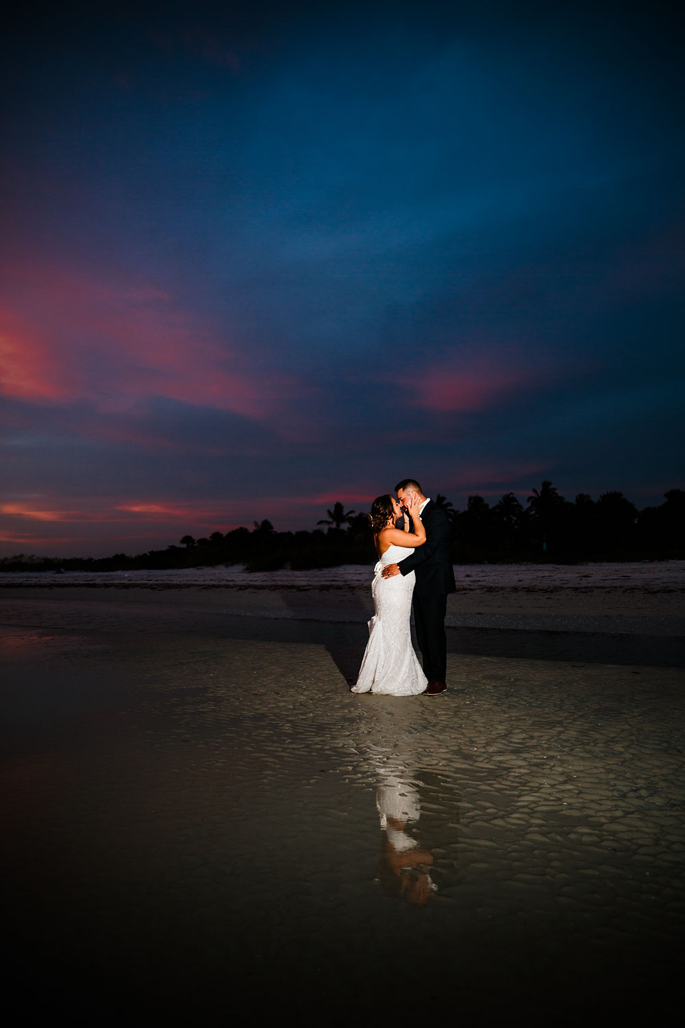 bride and groom kissing during sunset on beach