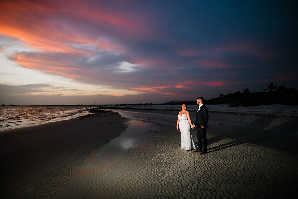 bride and groom smiling at each other in front of beach at ocean during sunset