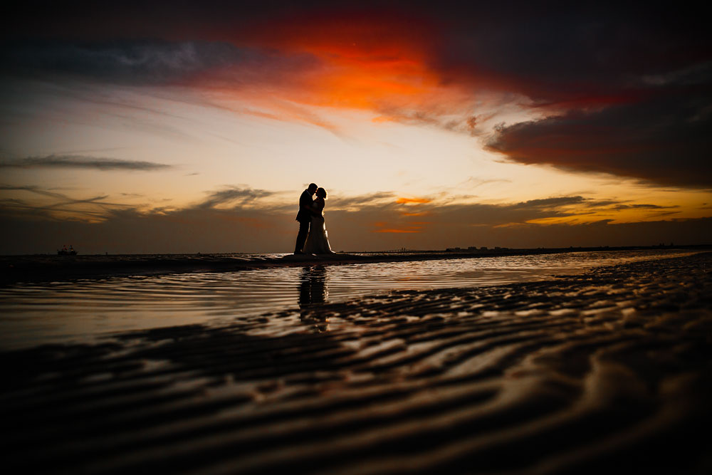 bride and groom kissing on beach during sunset