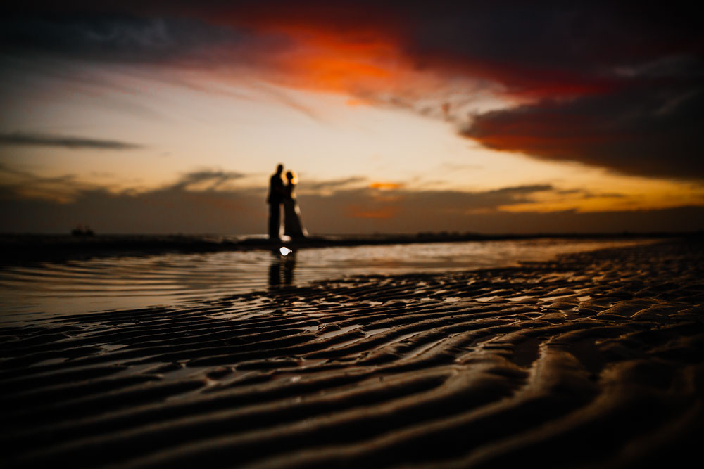 bride and groom hugging on beach during sunset