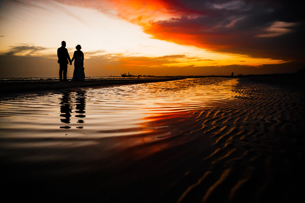 bride and groom holding hands on beach during sunset