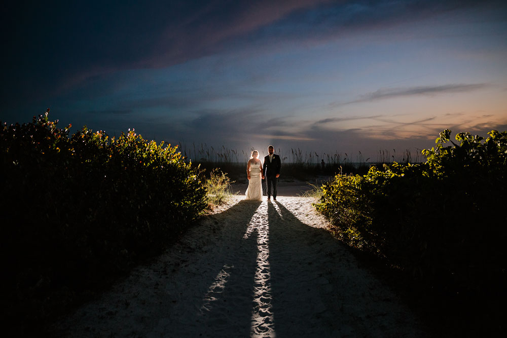 bride and groom holding hands on beach