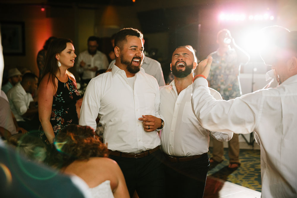 groom and groomsmen laughing and dancing at wedding reception