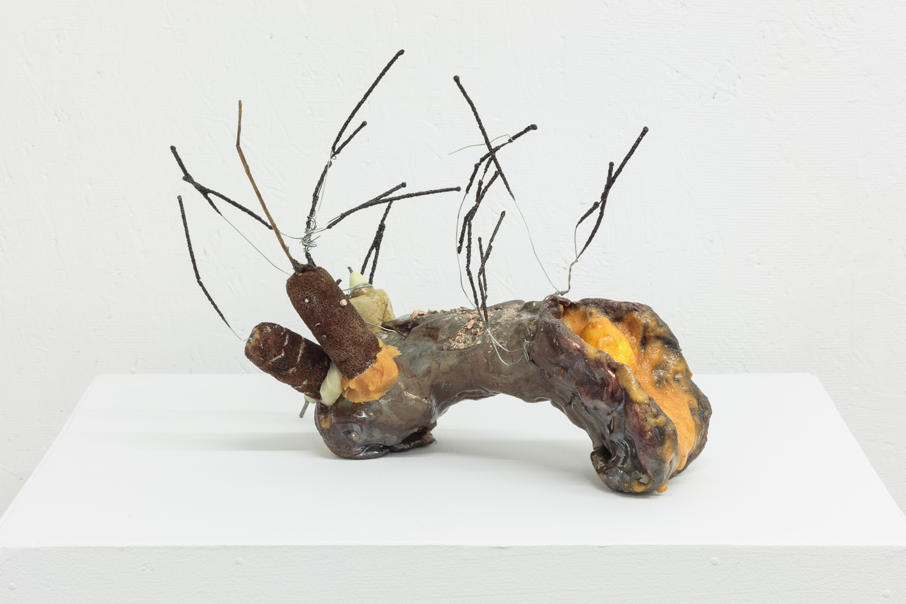 """F(akakt)ocaccia ,""  Giordano, 2016 - 2019. Glazed ceramic, Orange Tang, epoxy resin, artificial kumquat, cattails, nail polish, sparklers, shellac, leather, steel, wire hanger, contact lenses, bald eagle excrement, 13 x 10 x 10.5 inches. Photo courtesy of the artist and SARDINE."