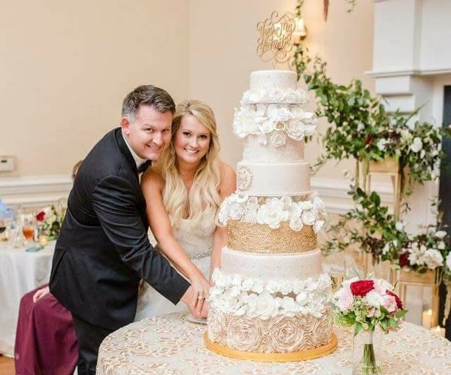 Couple cutting tiered wedding cake