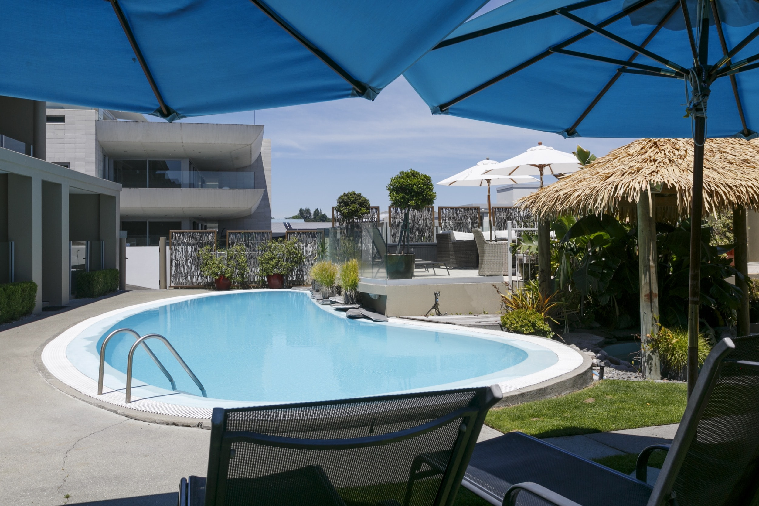 Pool area with heated swimming pool and thermal spa pool from BBQ area