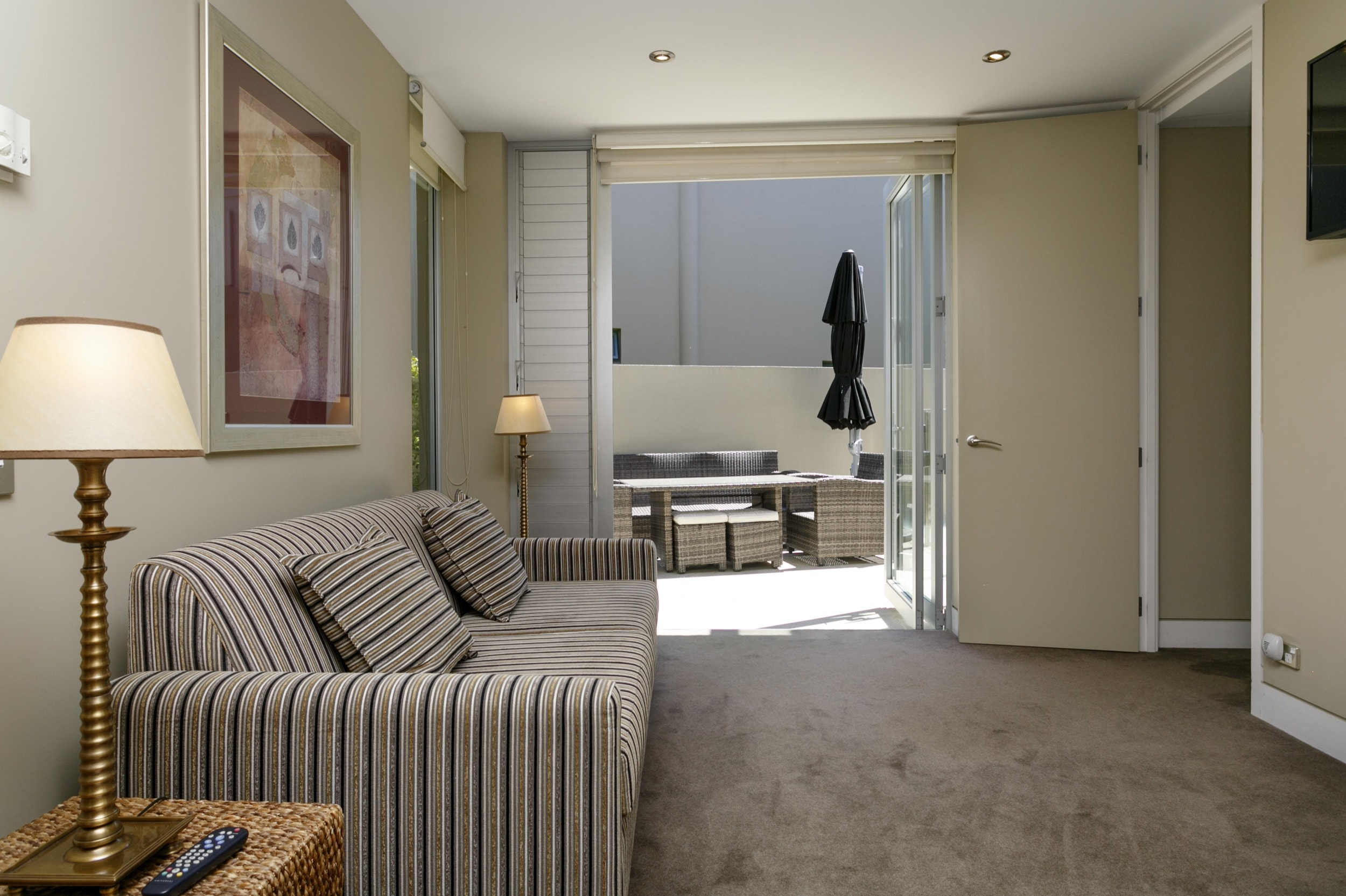 Ground floor two bedroom apartment secondary living area with sofa bed opening onto outdoor area.jpg