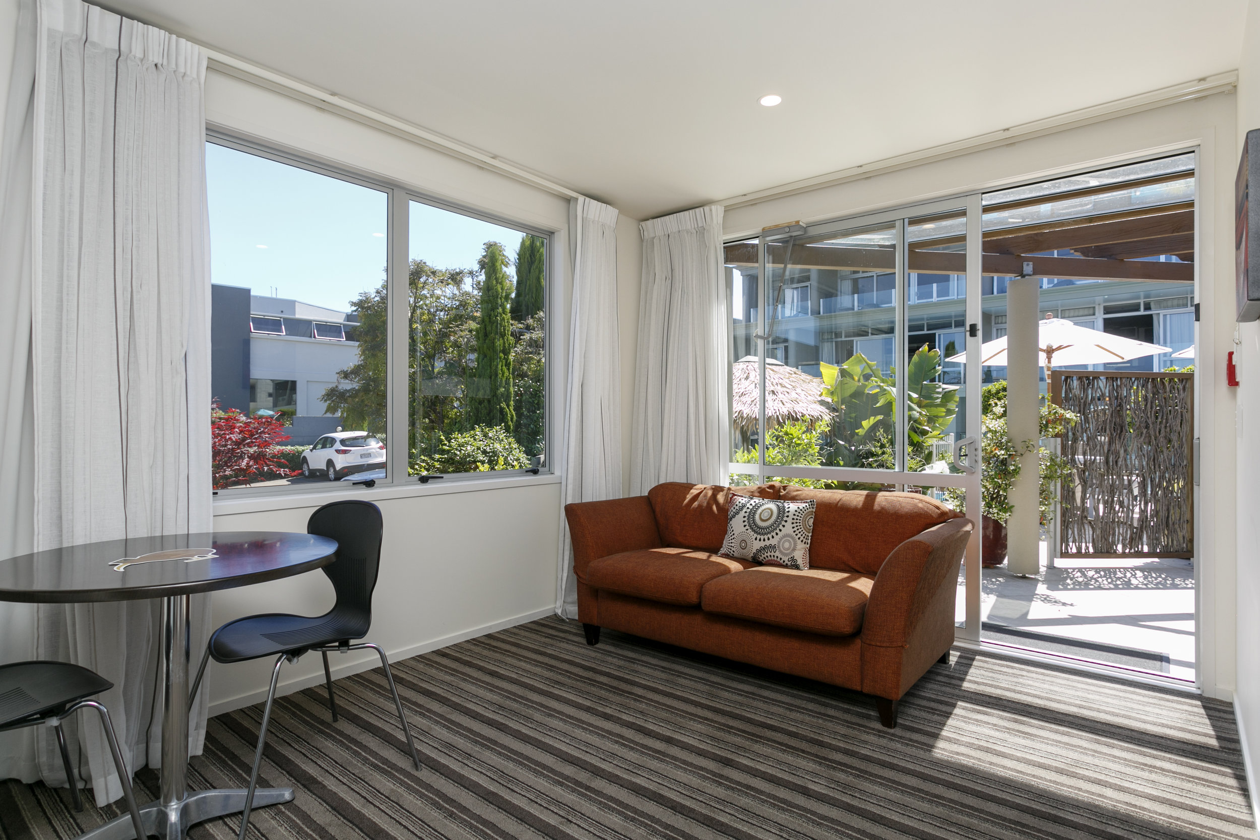 One Bedroom Gardev View living area looking out onto poolside patio area.jpg