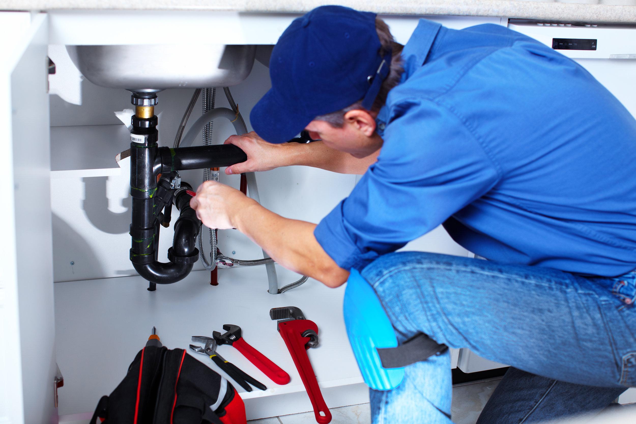Plumber repairing sink pipes