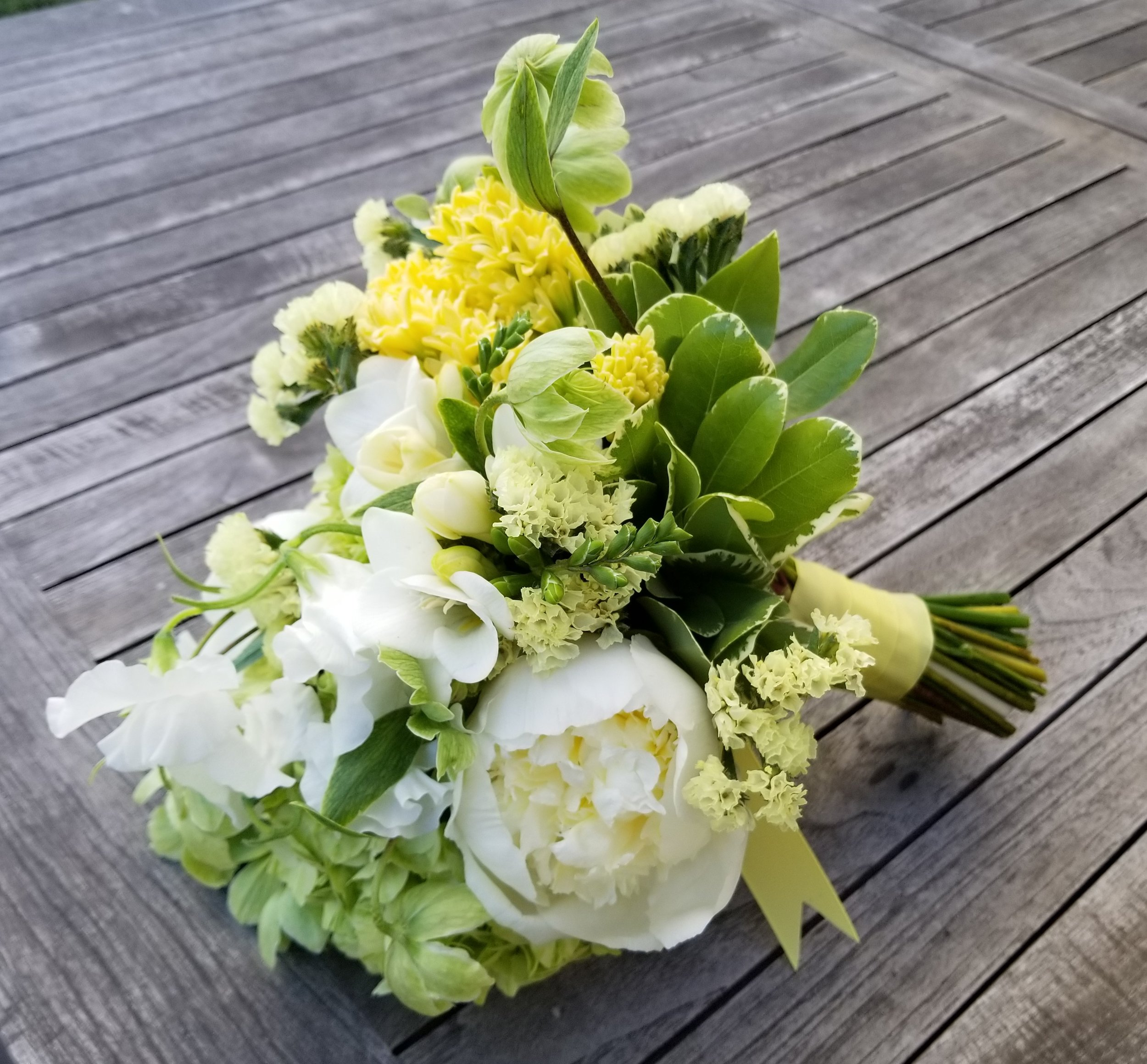 A spring hand-tied bouquet in yellow, green, and white.