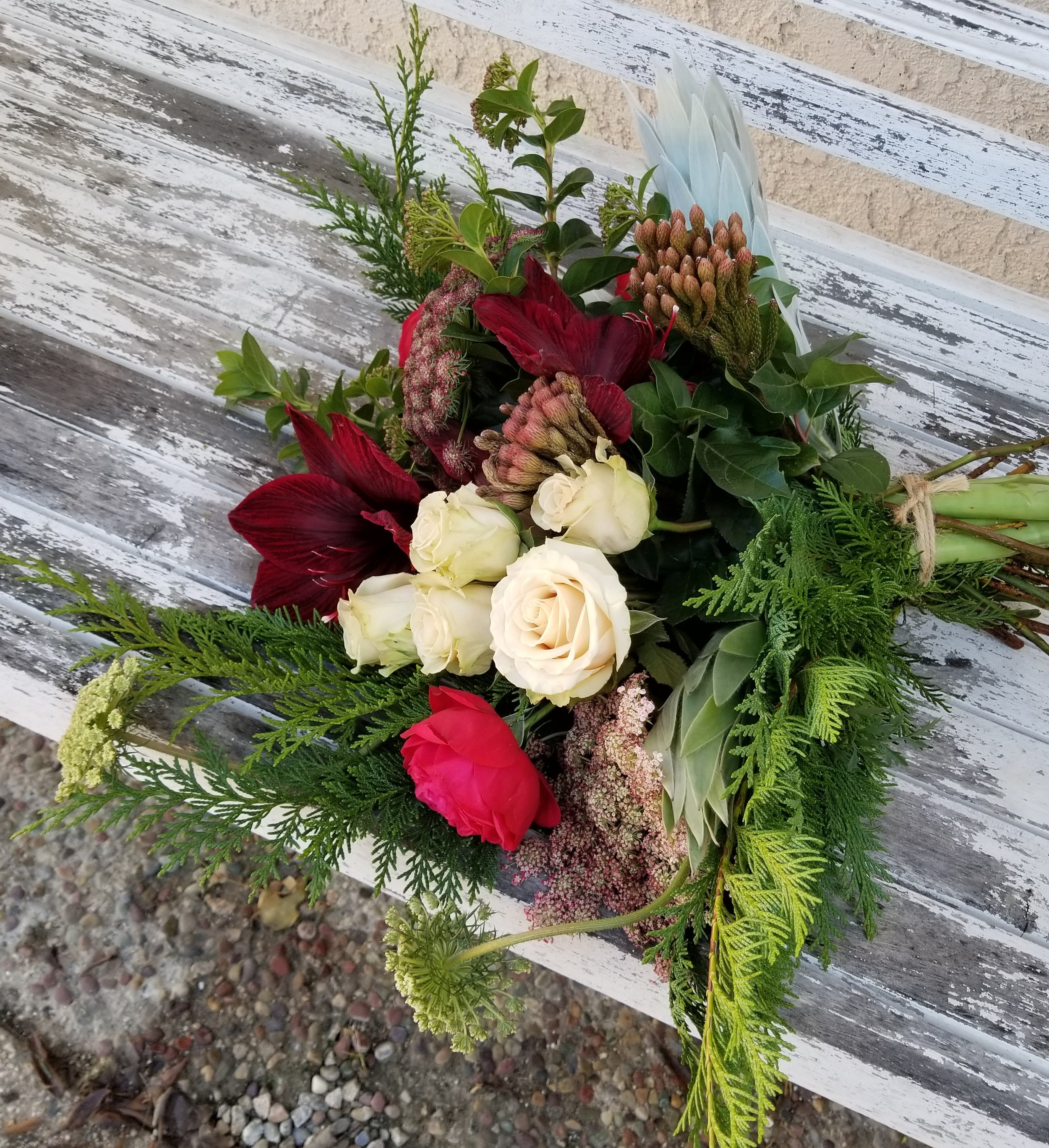 Wild & styled bouquet of roses, amaryllis, berzillia, chocolate lace, and lush greenery.