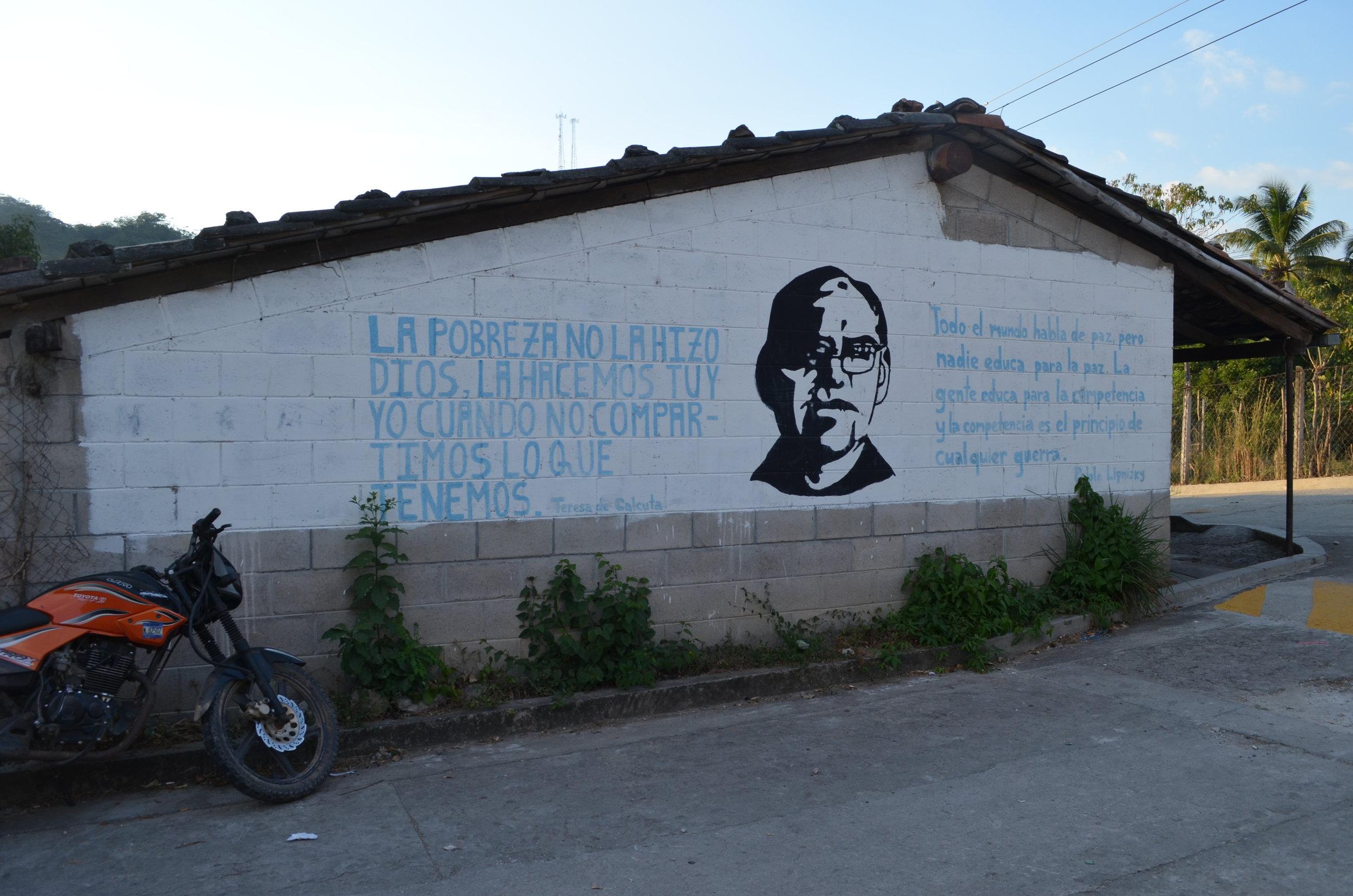 La pobreza no la hizo Dios, la hacemos tu y yo cuando no compartimos lo que tenemos. - Un mural en Arcatao. Foto por Dalton Anthony.