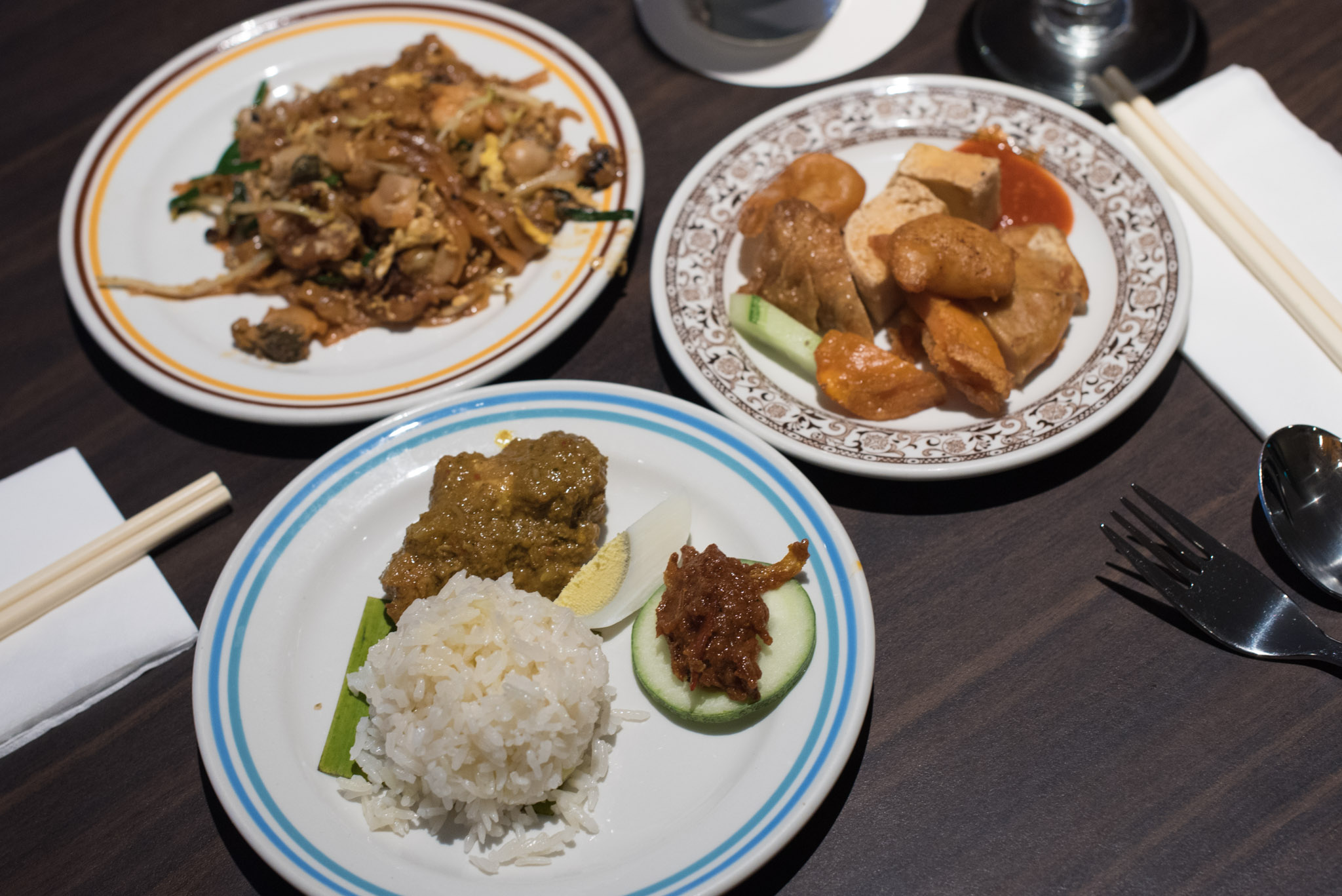 Clockwise from Top Left: Char Kway Teow, Lok Bak, Nasi Lemak with Nonya Chicken Kapitan Penang Hawkers' Fare - York Hotel