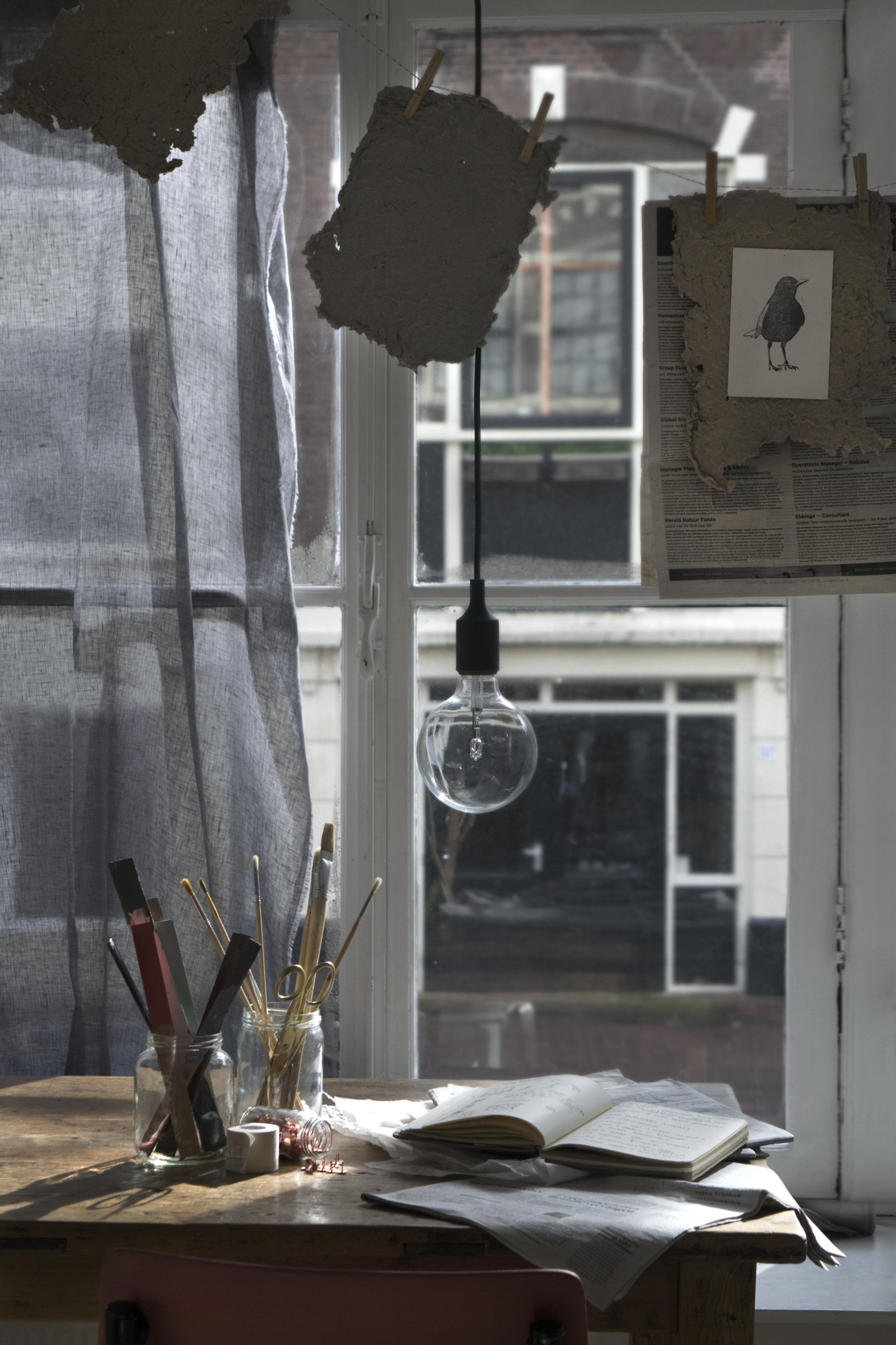 Stof ( evertgroot.nl ), papier aan waslijn,(afval Spuistraat, Amsterdam) krant (afval Herengracht, Amsterdam), anzichtkaart vogel ( agalab.nl ), hanglamp ( muuto.com ), Glazen potten (afval Singel, Amsterdam), houtstaafjes met verf, penselen, schaar, tape, punaises (eigen bezit), kranten (afval Herengracht, Amsterdam), notitieboekje (eigen bezit), tafel ( kieveen.nl ), stoel (unique pieces by  stylecookie.nl )