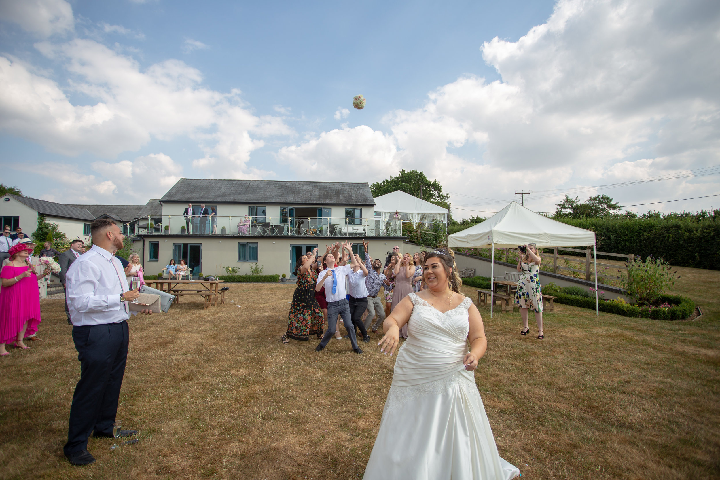 Sorcha throwing her flower bouquet in front of Manor Hill house, her guests were ready to catch it.