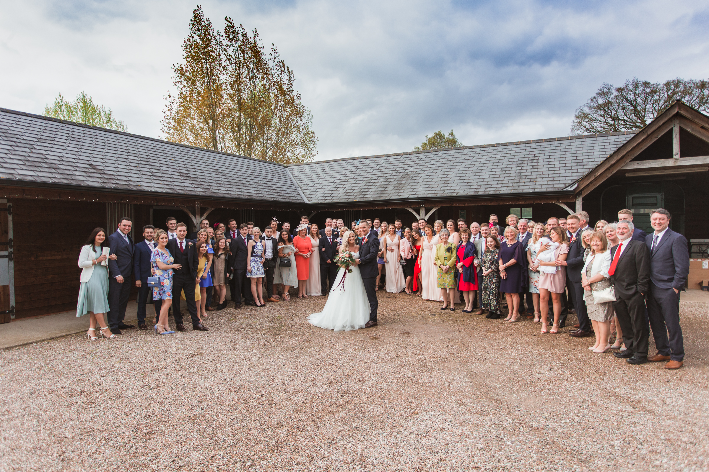 Colby and Kat in front of the barn at Manor Hill house in Bromsgrove, they are surrounded by all of their friends and wedding guests.