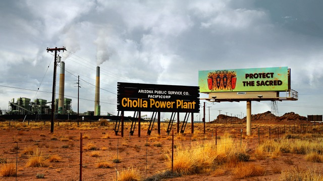"""The """" Remembering """" billboard stands unapologetically in front of the Cholla Power Plant on I-40, twenty-three miles East of Winslow, Arizona."""