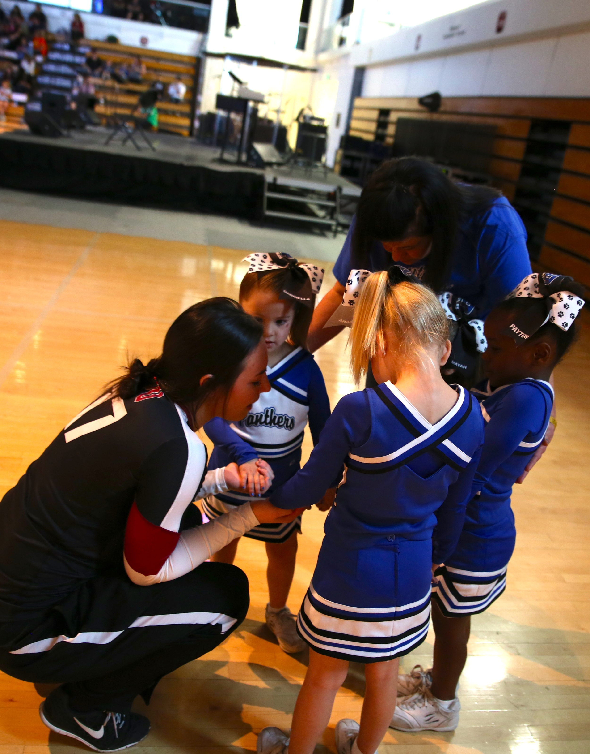 Coaches and staff praying with their girls before heading out onto the floor to compete. Cheering with a higher purpose.