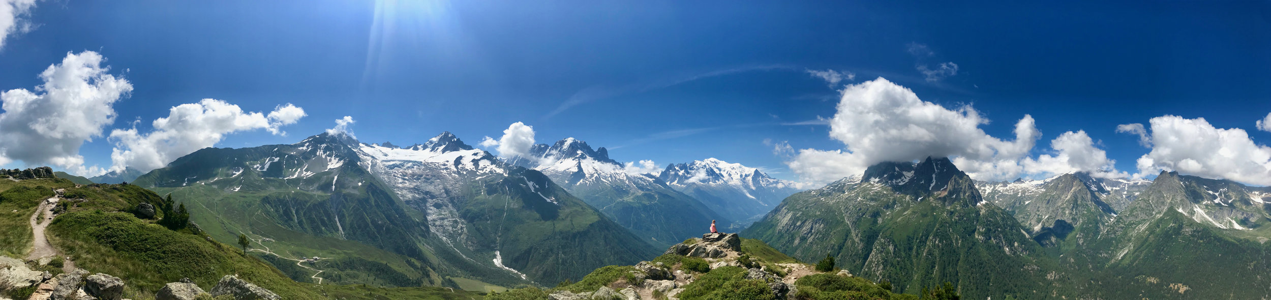 View from the Les Aiguillettes, looking out at the Mont Blanc massif. Mont Blanc is directly above Naomi (further away, hence it looks lower), and you can just about make out Chamonix in the valley to her right. Click on image for full-screen 4K quality