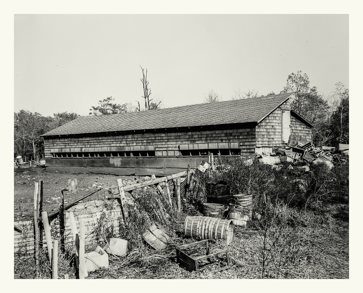 """Photograph No. PC 416. """"Photograph surveying barns and agricultural devices to be removed prior to construction of the Cohasset Naval Ammunition Depot Annex. (Note that barn has been cut in half as crews prepare for it's final removal.)"""" c. 1930; Records of Naval Districts and Shore Establishments, RG 181, NARA Boston."""