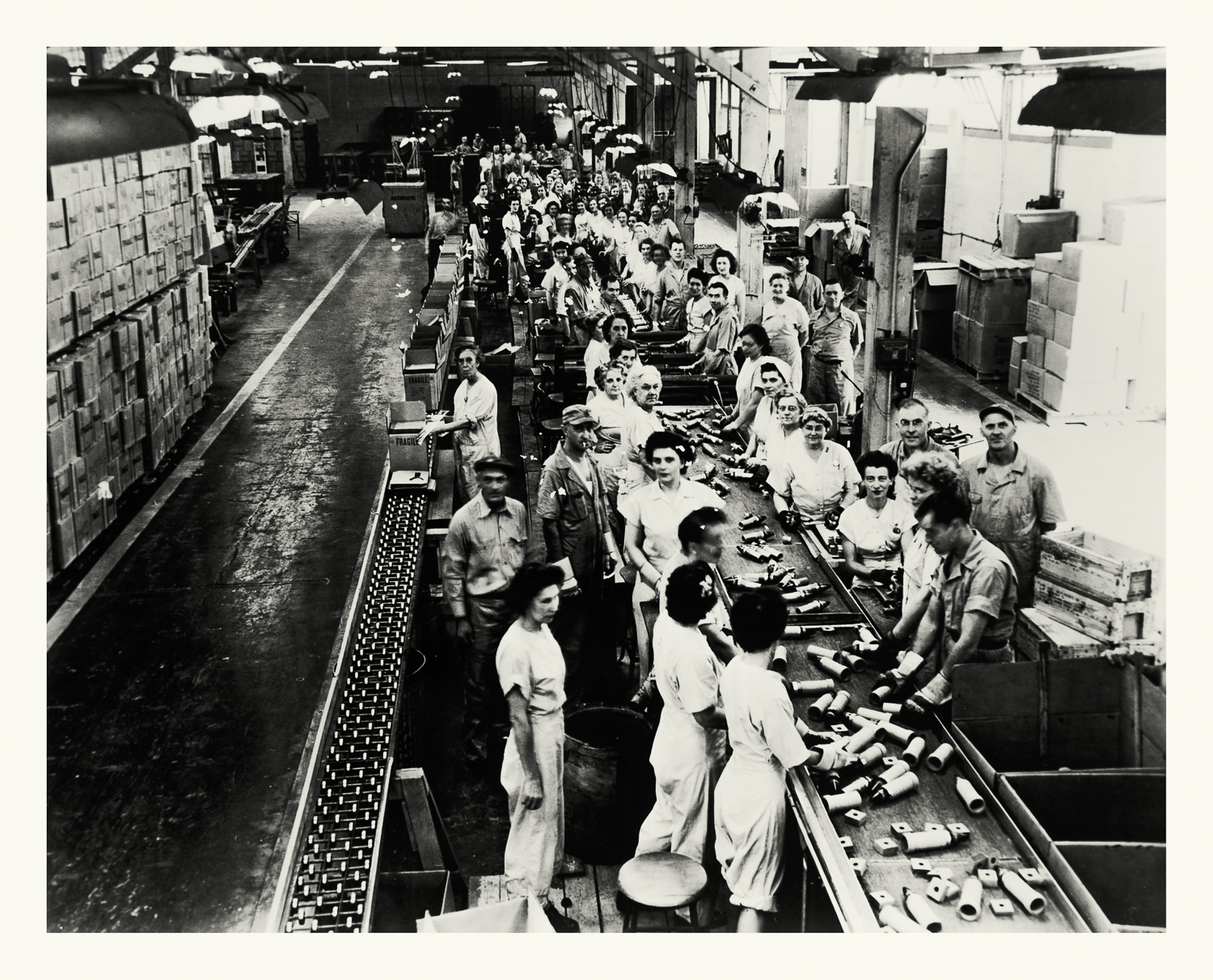 """Photograph No. PD 142. """"Photograph depicting a line of workers assembling Variable Timing fuses for rockets. These fuses used reflected radio waves to detect proximity to a target which would then trigger the explosion. Factory located at the Hinghan Naval Ammunition Depot"""" c., 1940 Records of Naval Districts and Shore Establishments, RG 181, NARA Boston."""