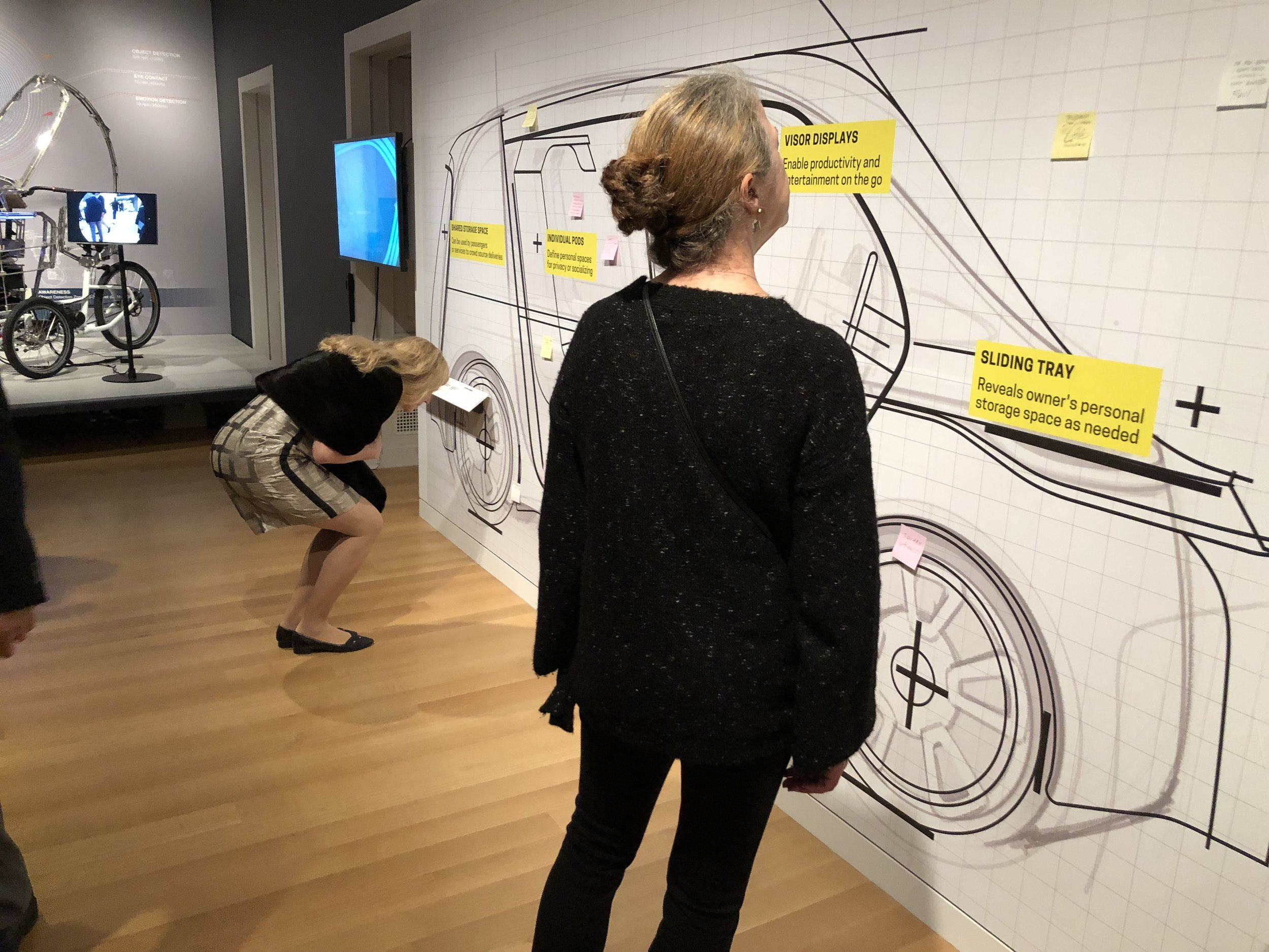 Visitors are prompted to capture their own hopes, needs and desires for future mobility on post-it notes and to place them upon a life-sized sketch of a vehicle designed to support shared mobility.