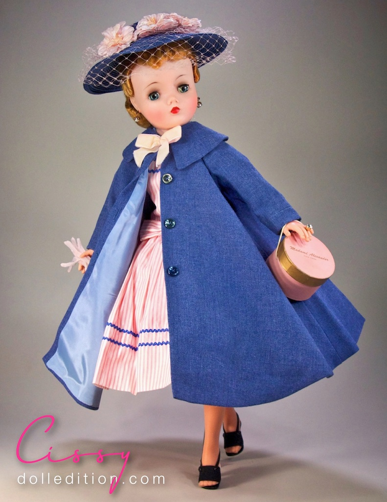 Cissy is wearing a 1958 #21-48 woven blue swing coat with wide collar and  coordinating hat that came with the boxed set. Cissy is wearing a shell pink ticking cotton dress with dusty blue rick rack trim.