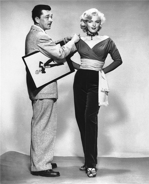 Marilyn Monroe with costume designer William Travilla with sketch for pants costume for Gentlemen Prefer Blonds.