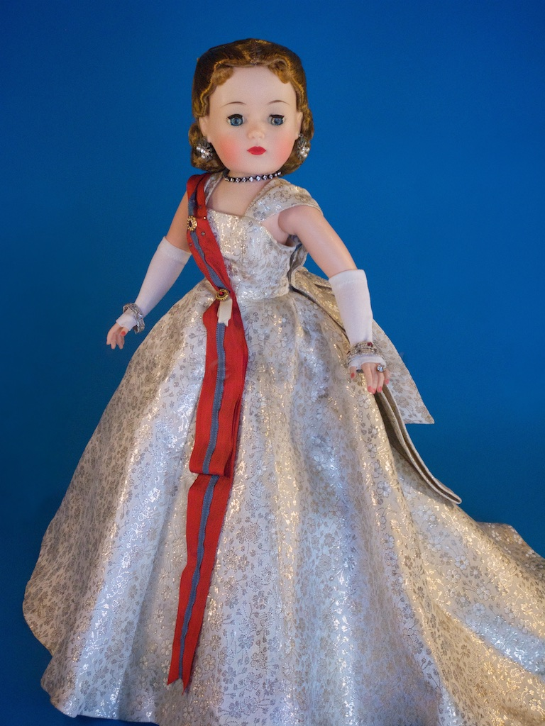 "There was also a variation of the same queen with a ""Sleeping Beauty"" face. She is No. 2170 vs. the Cissy Queen No. 2180. The dolls clothing tag reads ""Madame Alexander"". This example does not have her crown. The metal crowns, used from 1960 to 1962, were literally pinned into the dolls wig cloth base and were easily misplaced if they ever came off."
