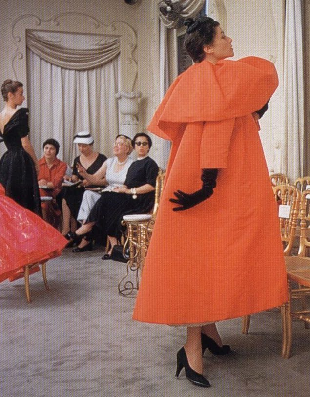 Cristobal Balancinga and his interpretation of the swing coat as an evening-coat... Love the ladies in the background still in their Mamie Eisenhower mid west fashion.