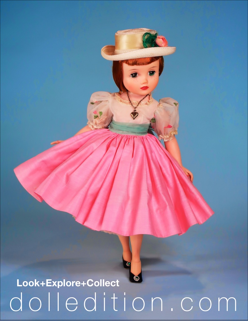 Looking demure in her party frock of cotton and organdy top with embroidered details, Italian straw hat accented with a feathers and a pink rose.