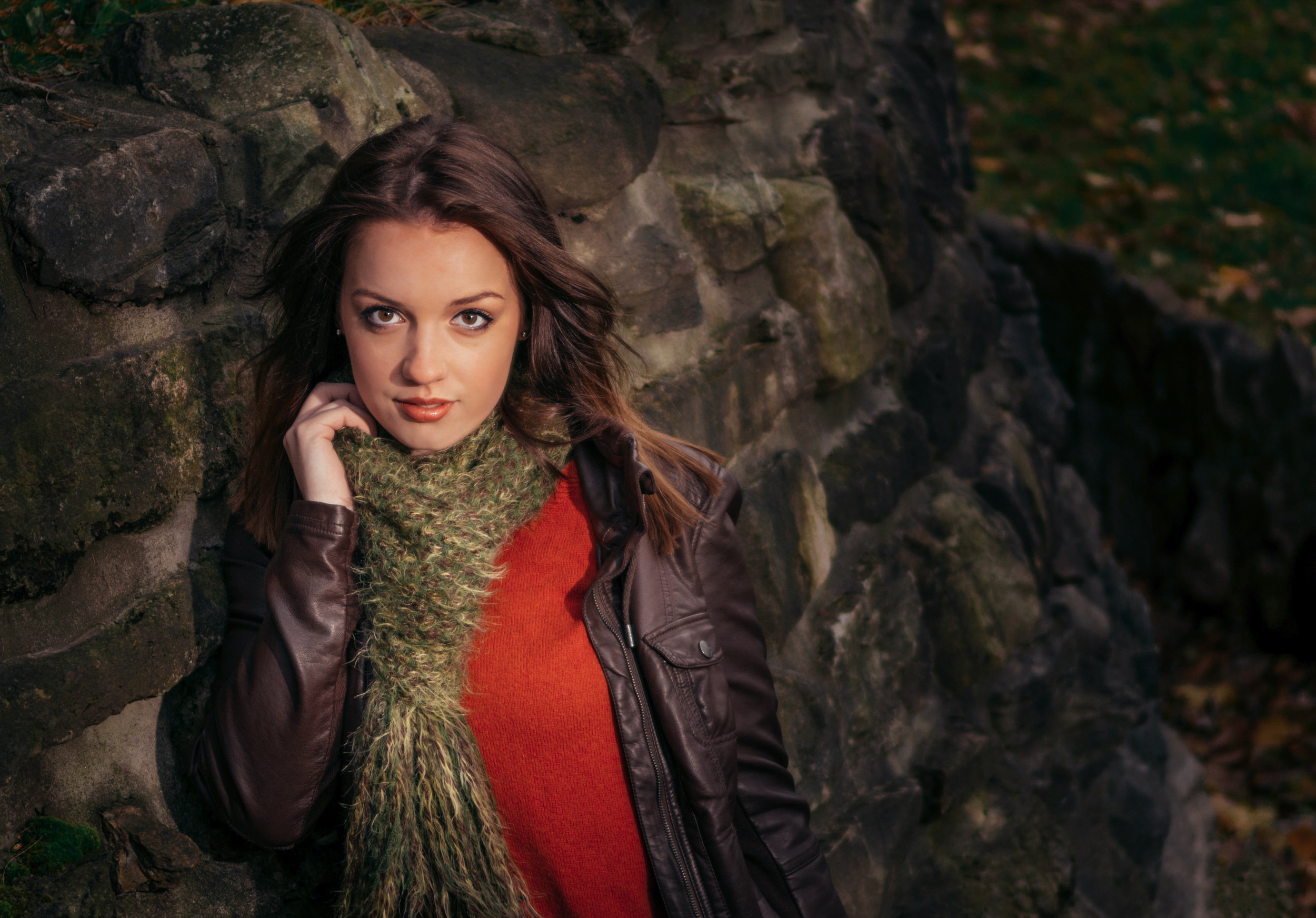 female model posing next to tree in park with scarf