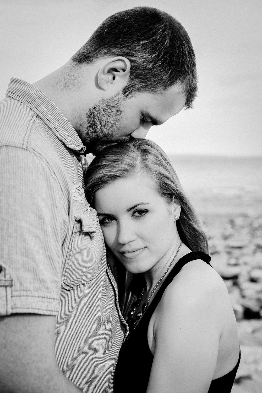 man kissing woman's head at beach