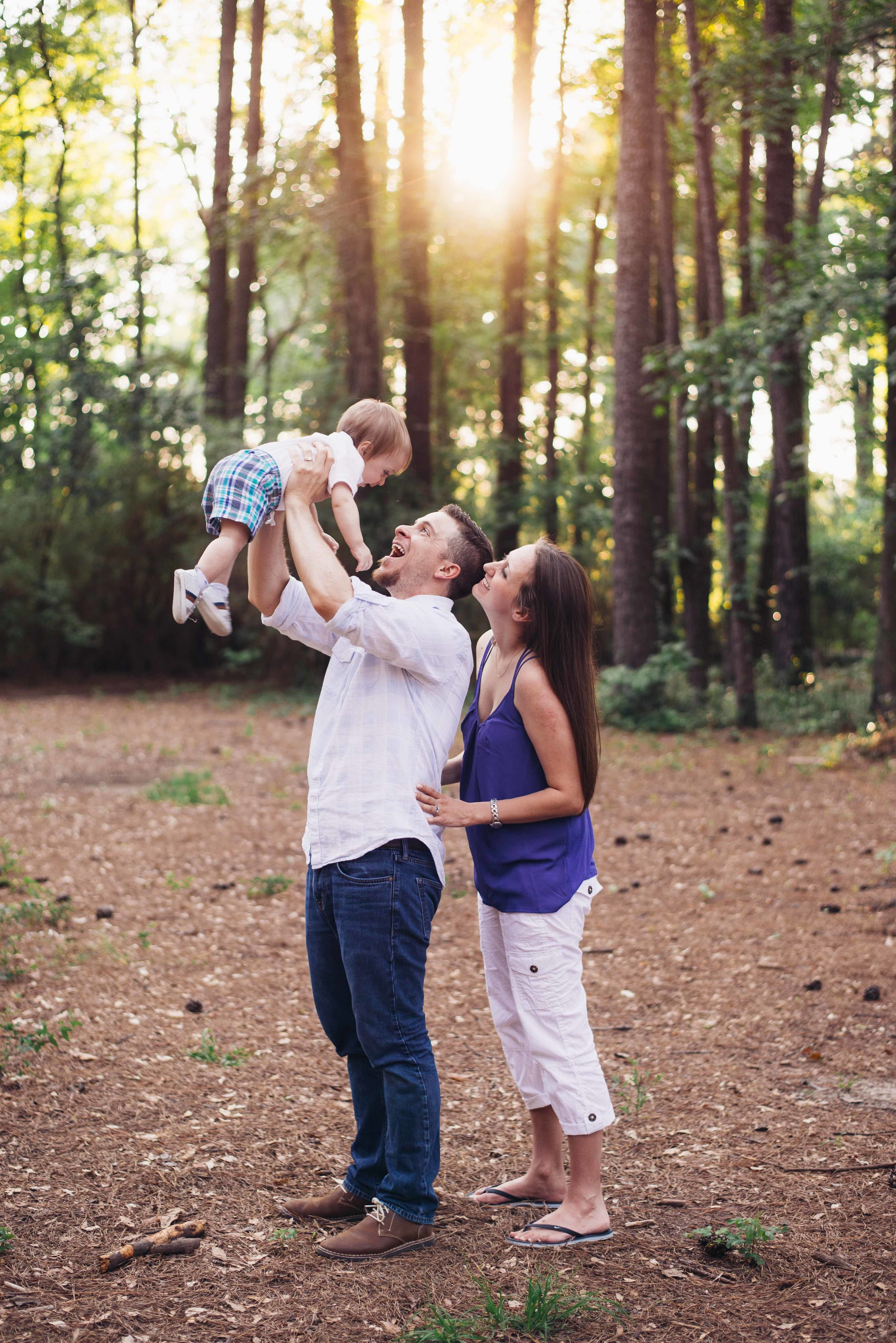 couple throwing child in air for portrait