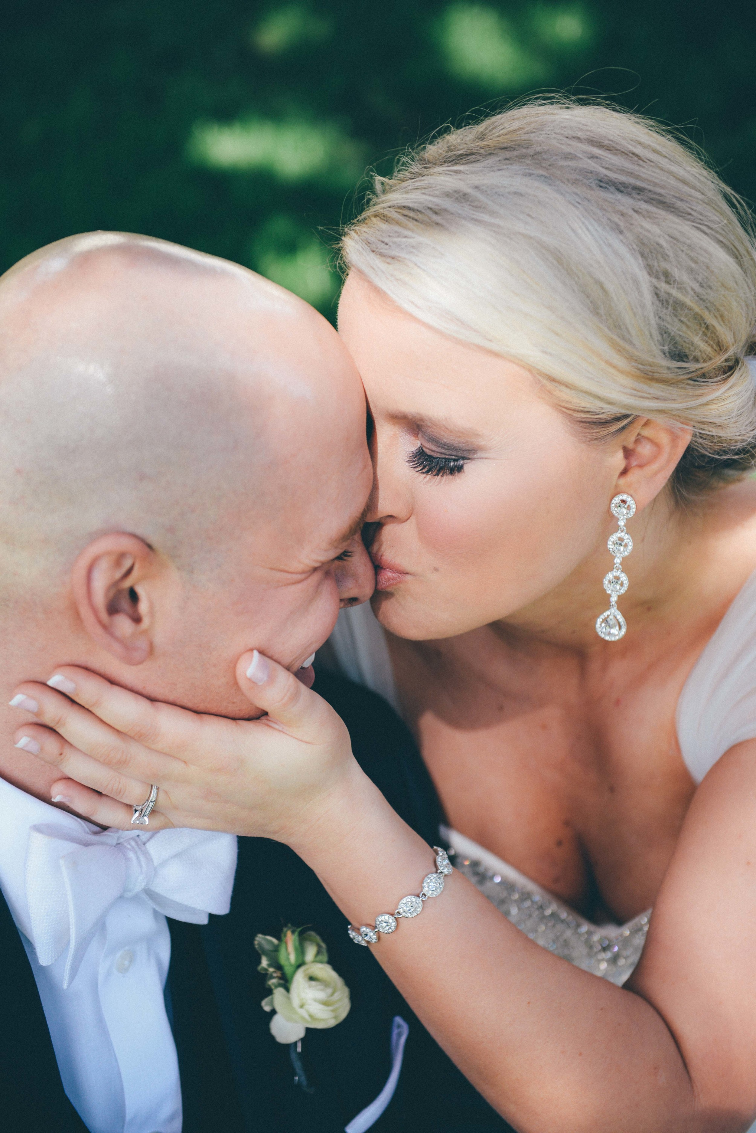 bride and groom kissing smiling hand on face