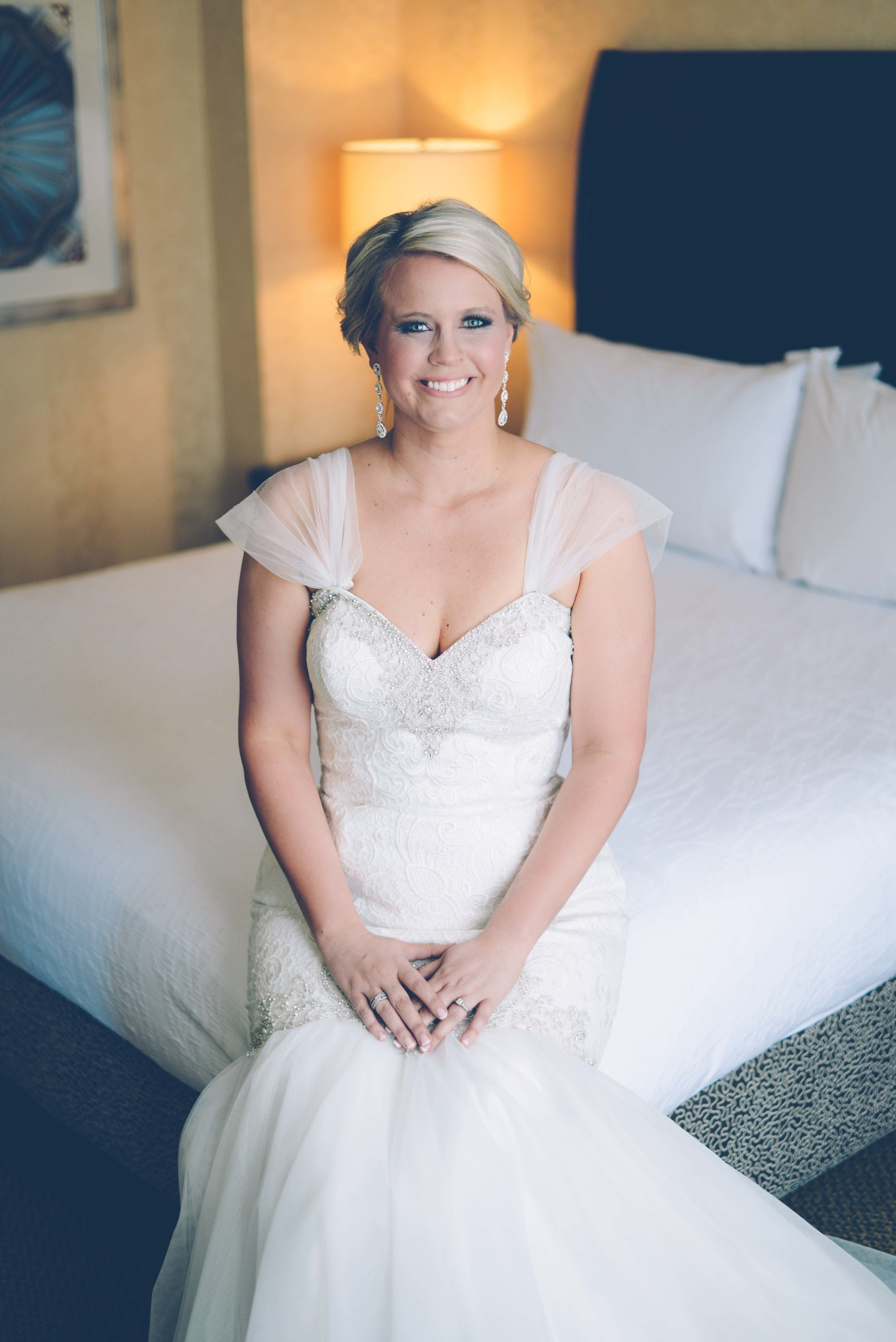 bridal portrait of bride sitting on hotel bed