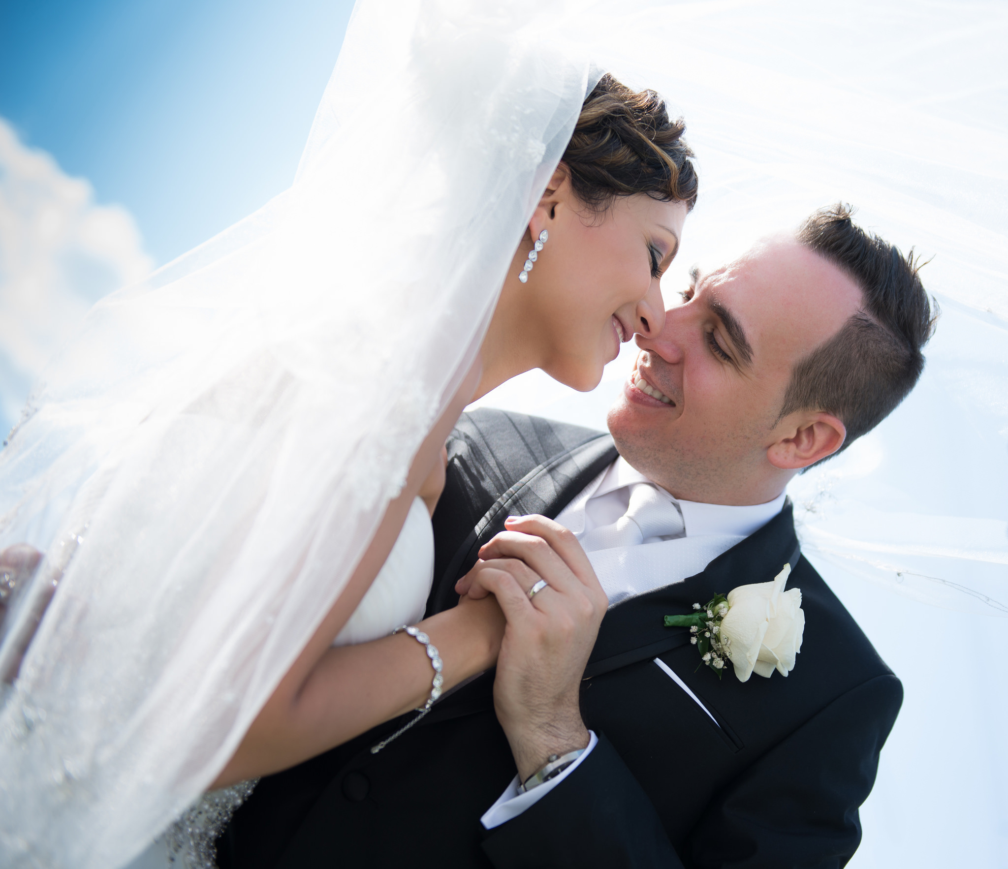 bride and groom kissing under veil with blue sky in the background