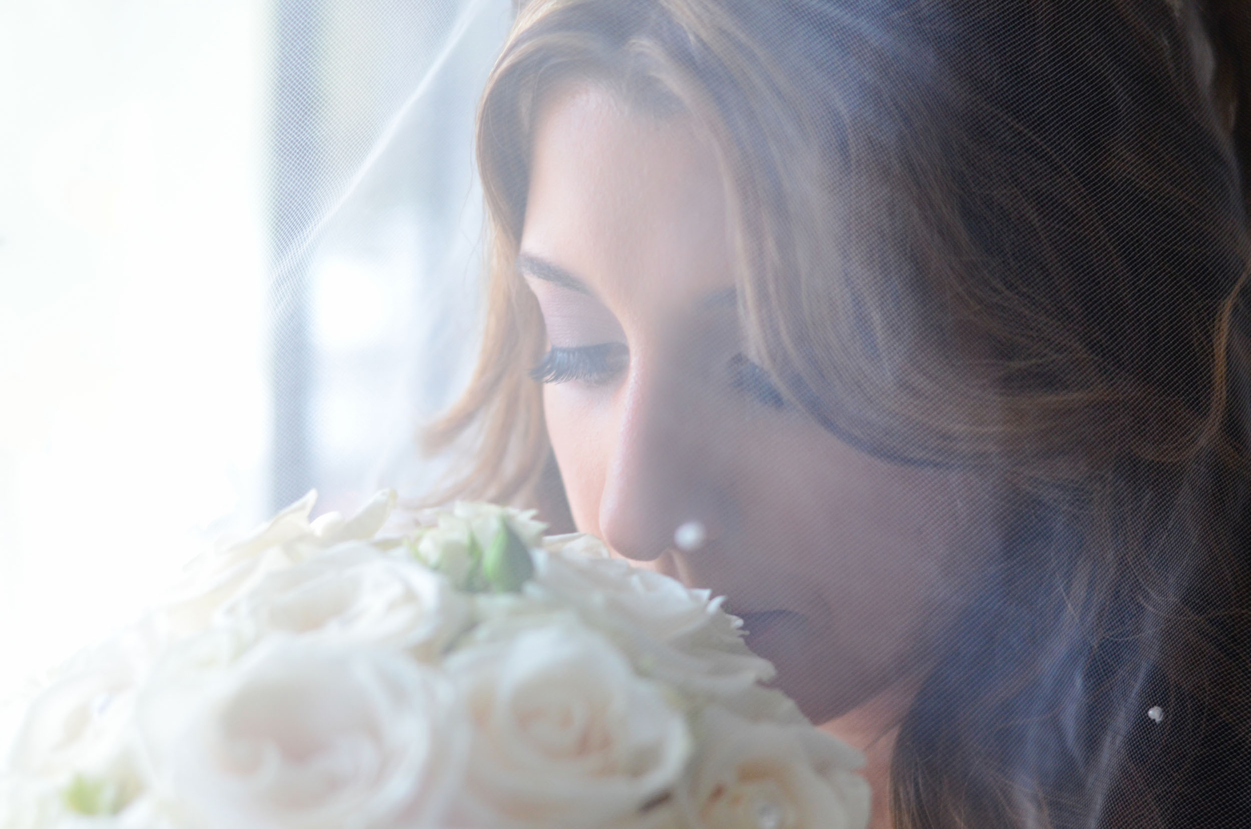 bride smelling flowers under veil by window