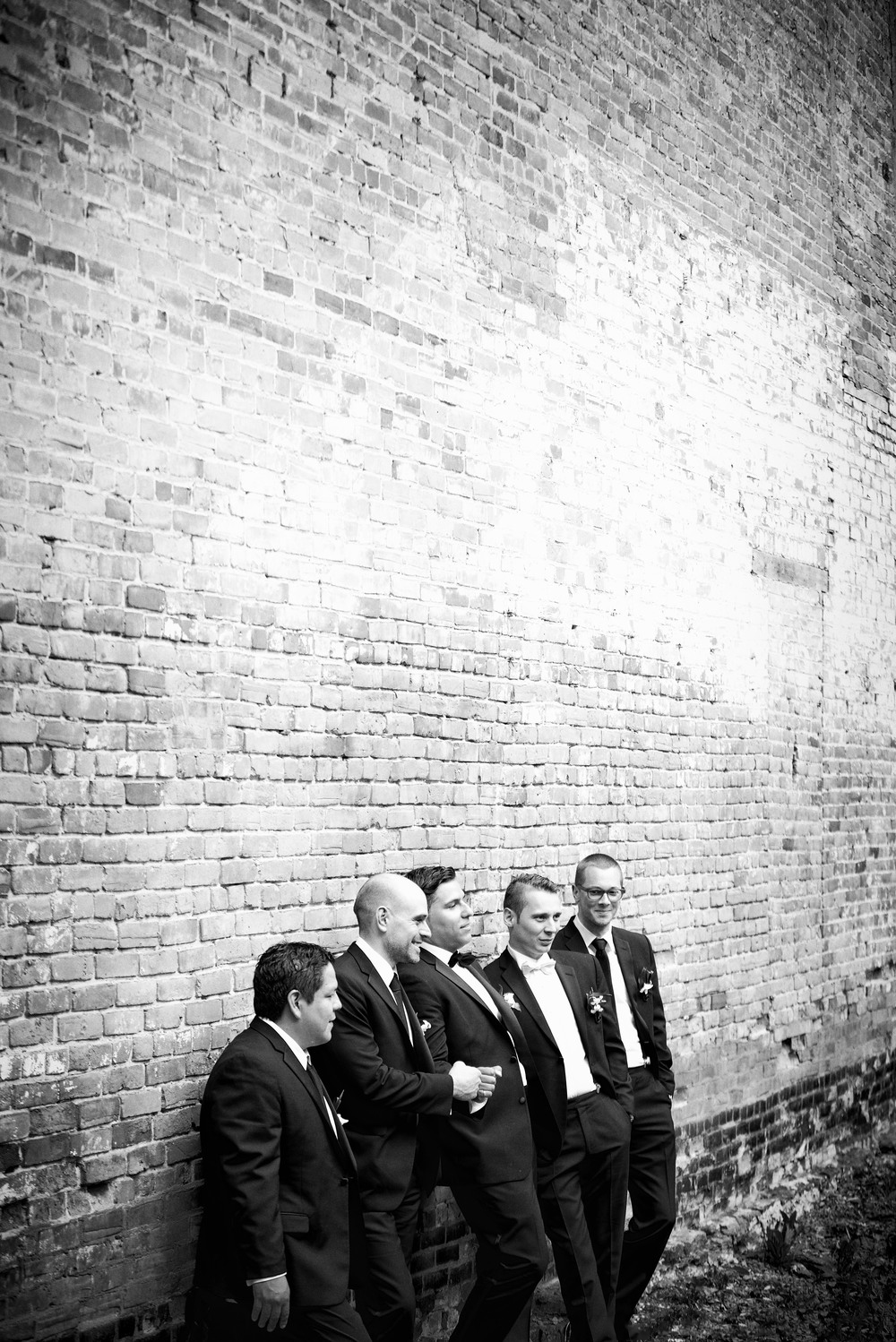 groomsmen leaning against brick wall in monroe, la