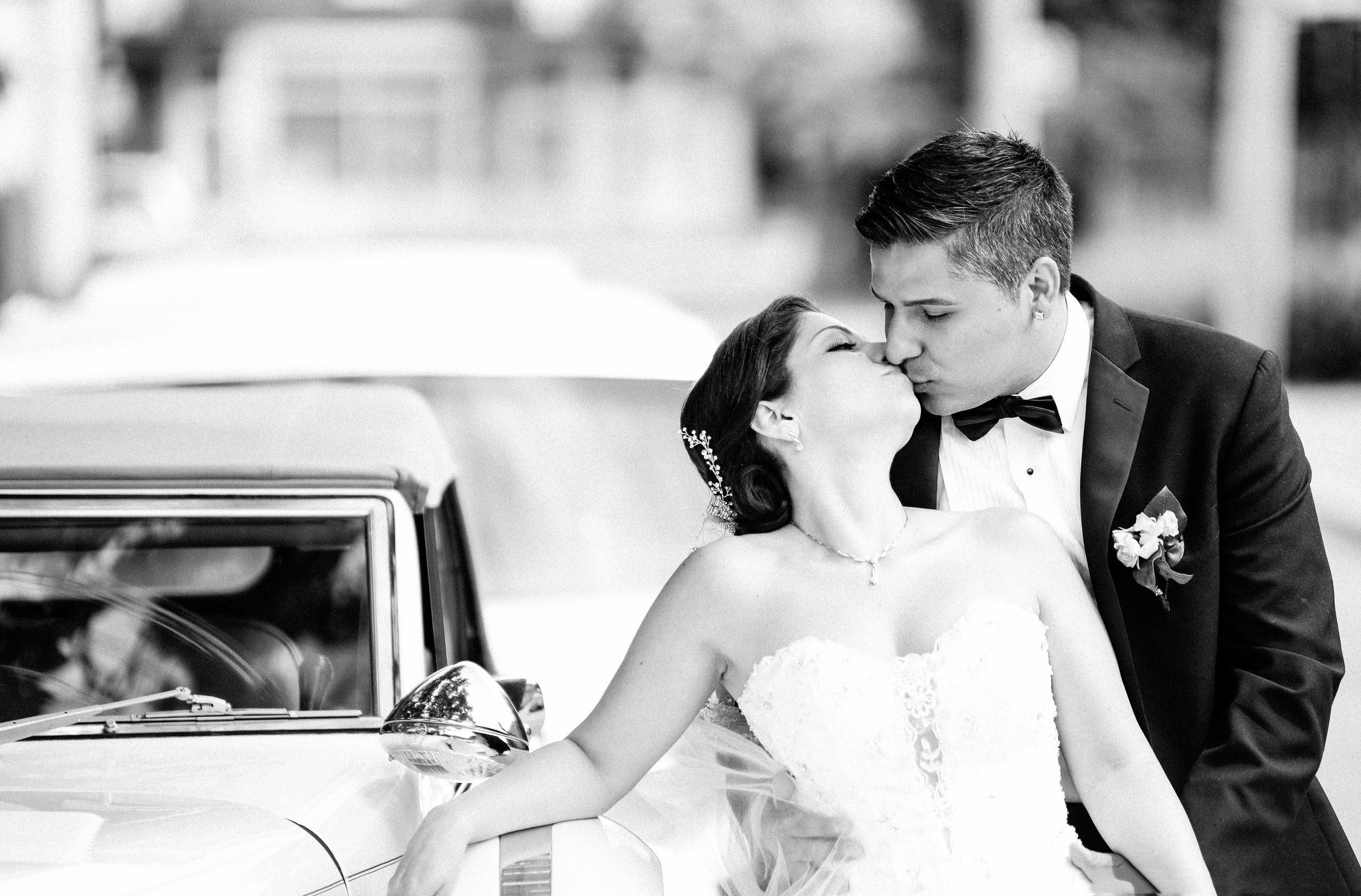 bride leaning against limousine while groom kisses her