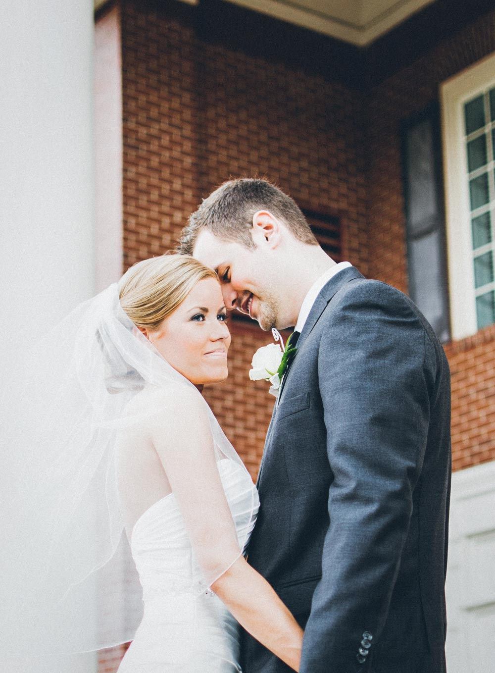 bride and groom touching foreheads in front of church