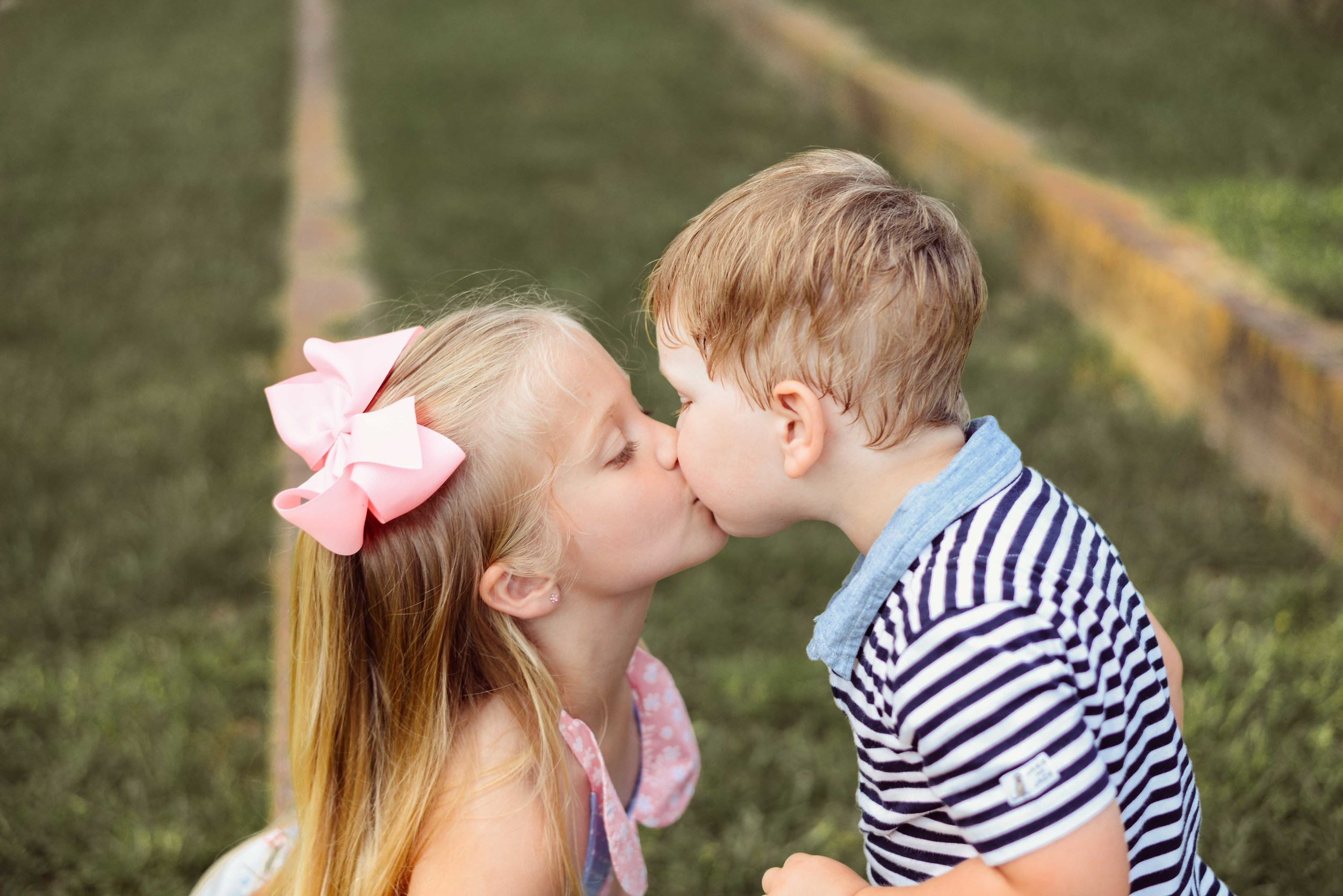 brother and sister kissing at park