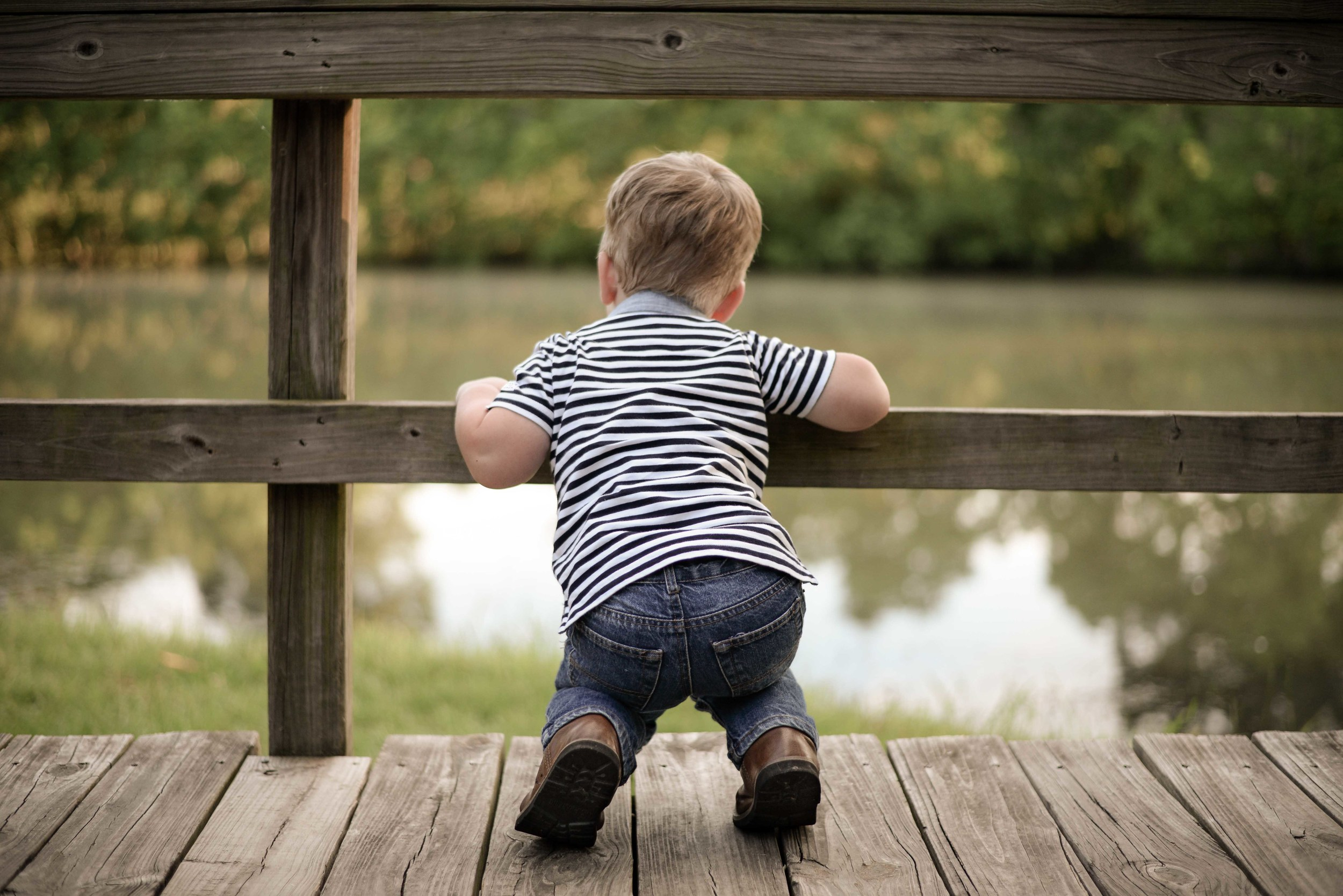 southern boy in jeans and boots looking at pond