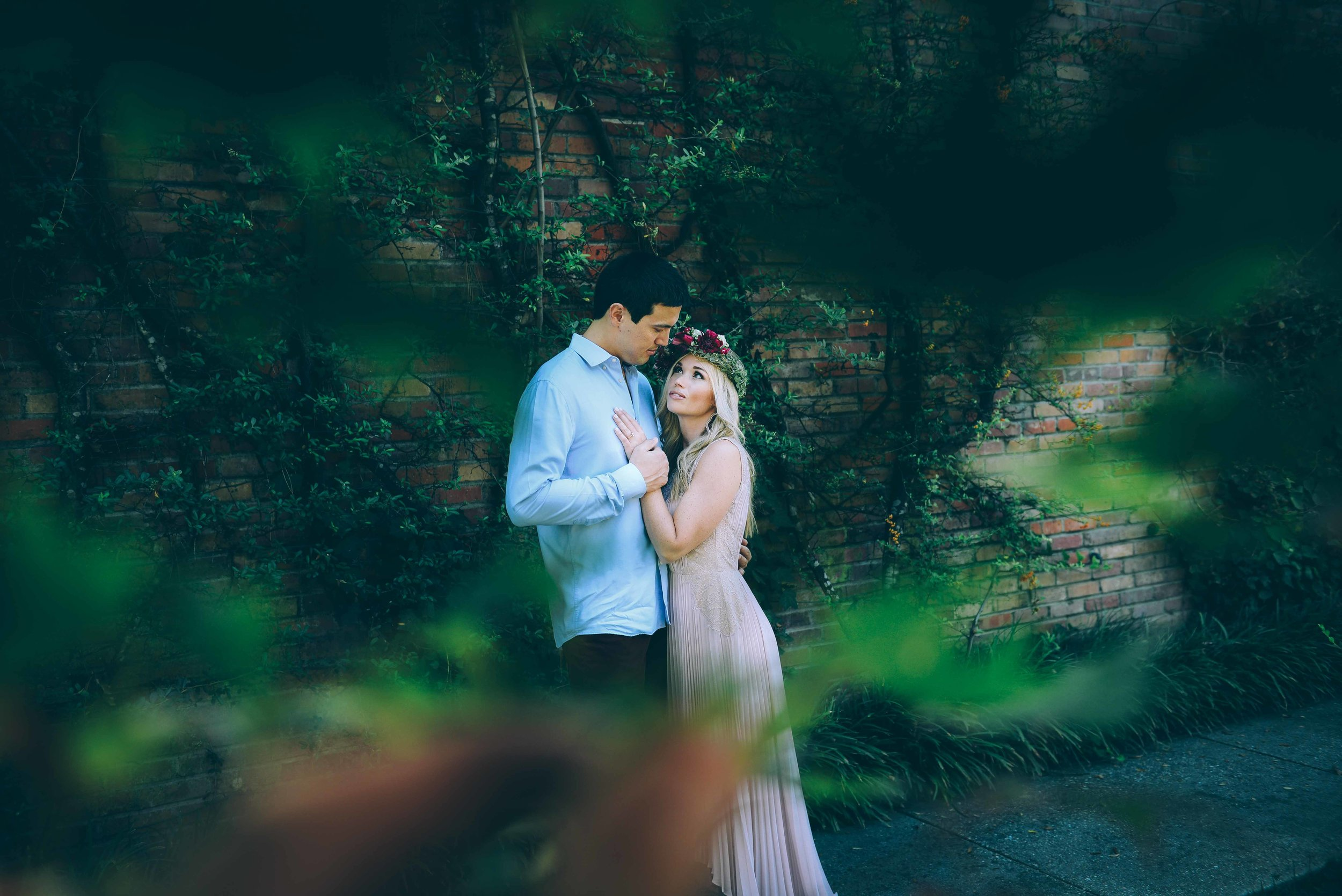 engaged couple standing in front of wall with green vines