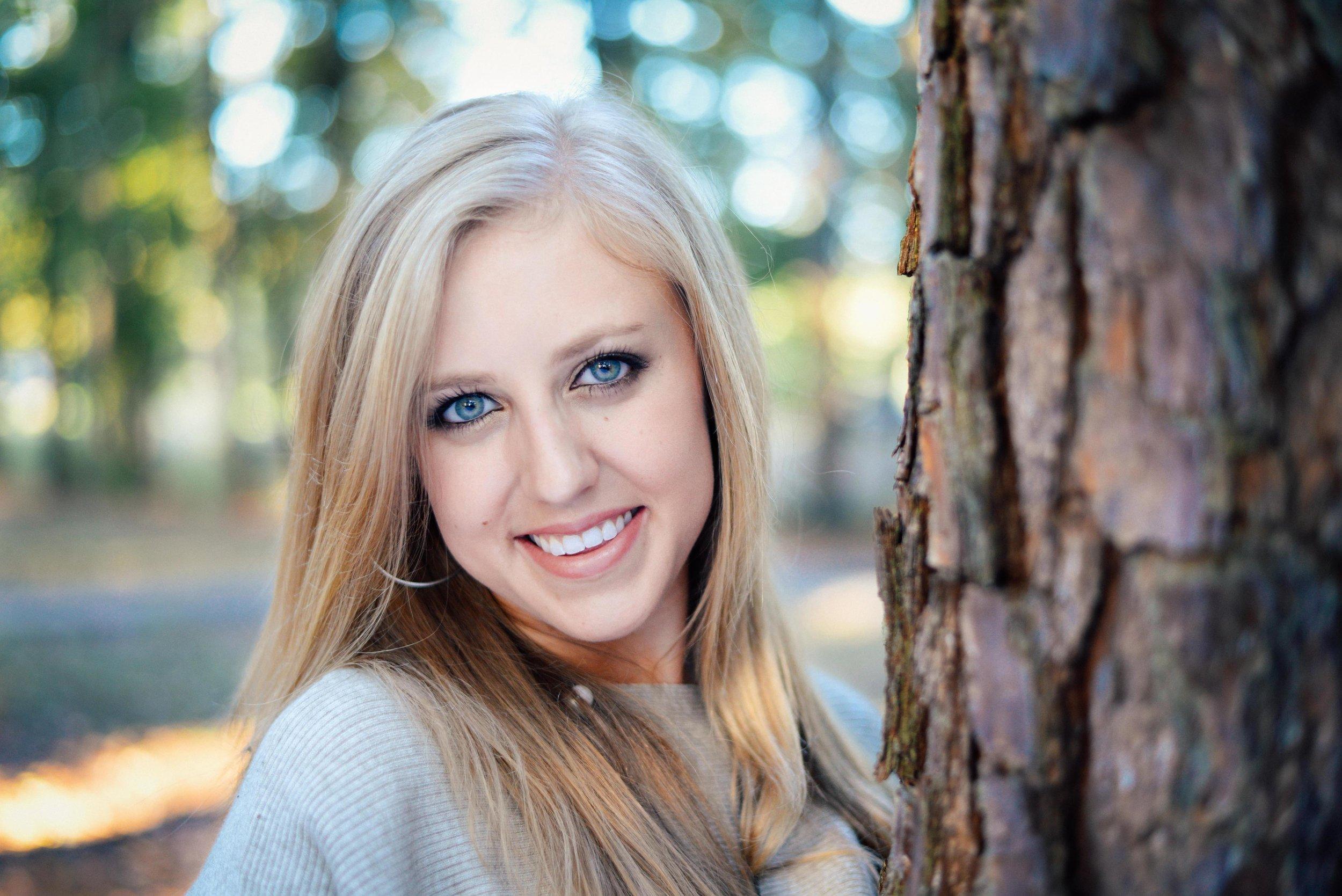 blonde girl leaning against tree
