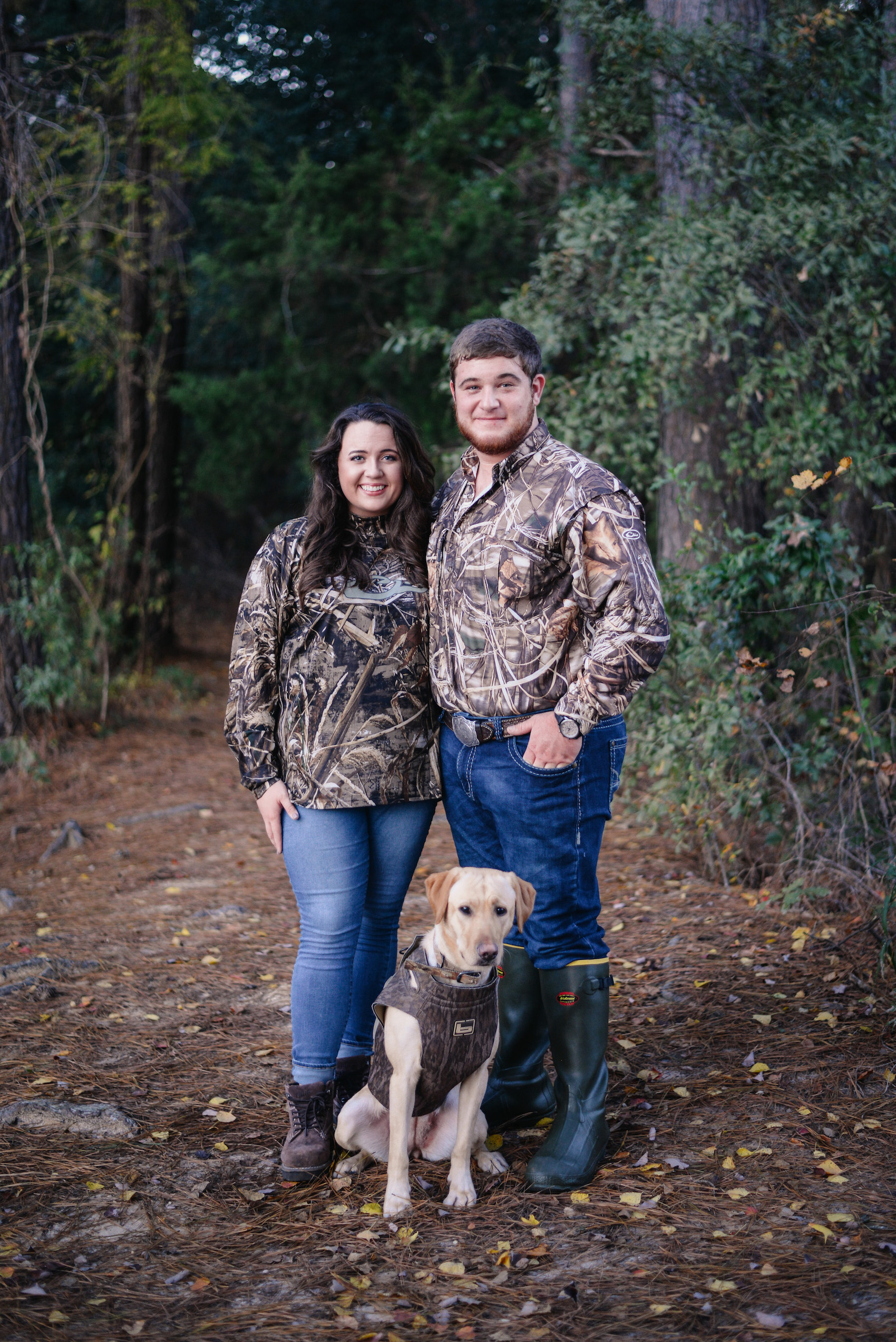 engaged couple in camo with dog